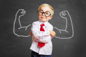 Glückliches Kind vor Tafel mit Muskeln aus Kreide dahinter