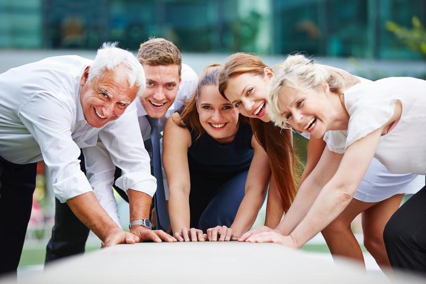Zusammenarbeit im Business Team mit lachenden Mitarbeitern im Freien